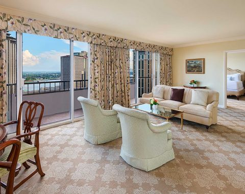 The living area in the Presidential Suite, including elegant furniture and a private balcony with a Mississippi River view