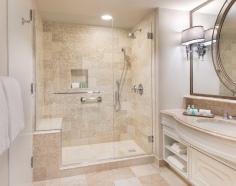 View of a luxury bathroom in the Windsor Court Hotel with a shower plus elegant mirror and countertop with Italian marble