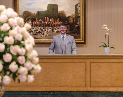 Large bouquet of roses and friendly desk attendant in the lobby of the Windsor Court Hotel