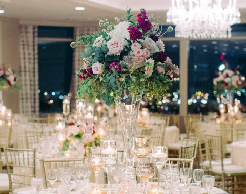 An evening event in La Chinoiserie at Windsor Court Hotel, with large violet and pink floral centerpieces on candlelit tables
