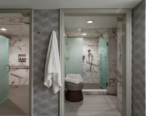 View of the luxury showers in Spa at Windsor Court, featuring grey and white marble tiles throughout