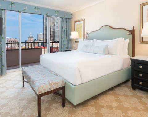 Deluxe Suite at Windsor Court Hotel, with a king size bed, tv and view of the New Orleans skyline from a private balcony