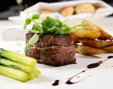 A plate of dinner at The Grill Room, including steak, french fries, and asparagus