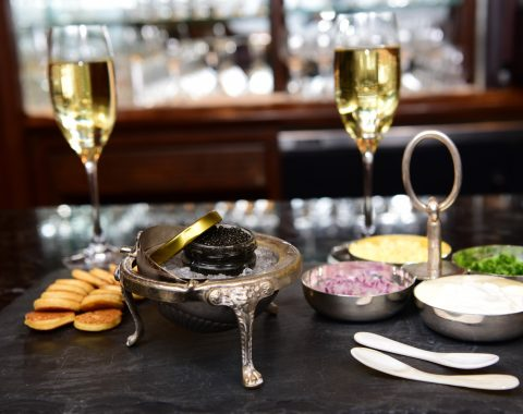 Caviar display including mother of pearl spoons and other accoutrements as well as two glasses of sparkling wine