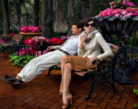 Nicely dressed couple sitting outside in the courtyard at Windsor Court Hotel in New Orleans